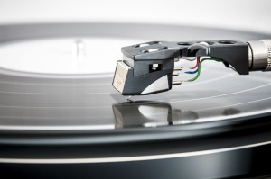 Close-up photo of a record player's needle touching a vinyl record.